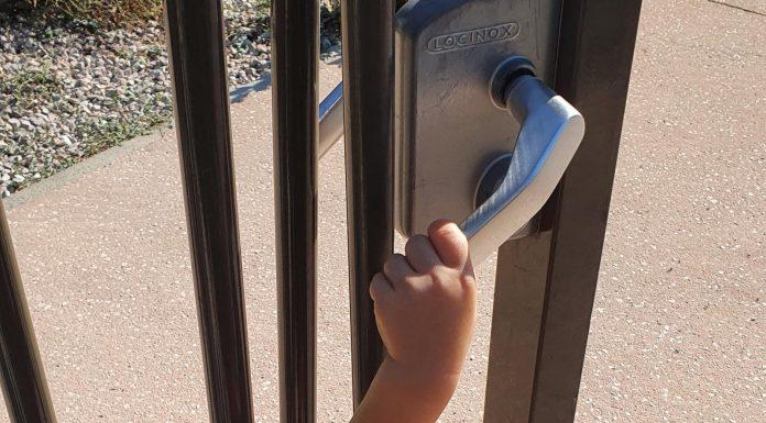Main d'enfant jouant avec une porte